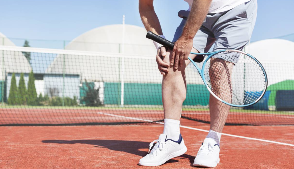 A tennis player holding his knee needing prolotherapy