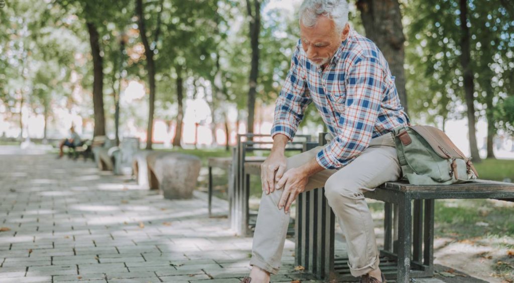 A man sitting on a bench with knee arthritis symptoms