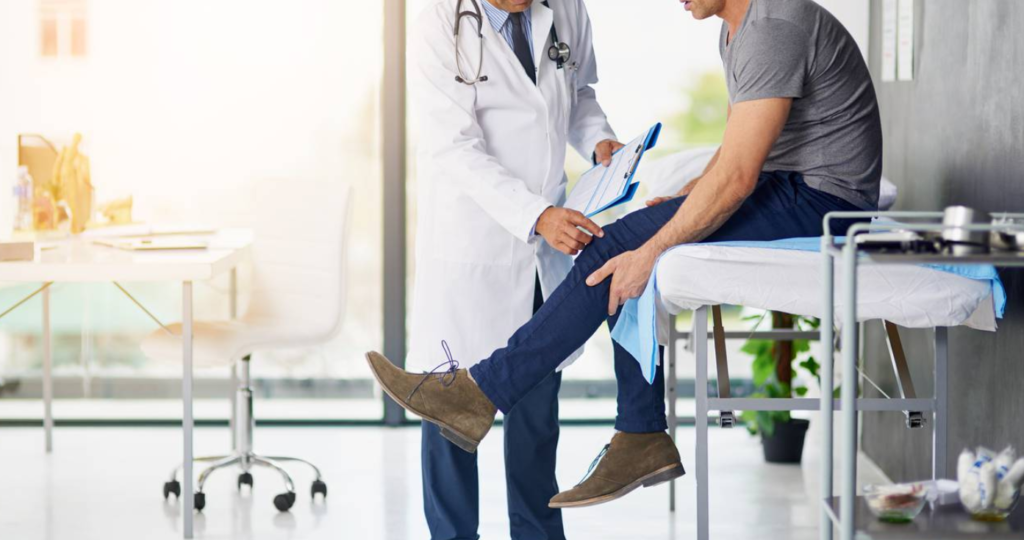 A doctor examining a man with knee osteoarthritis