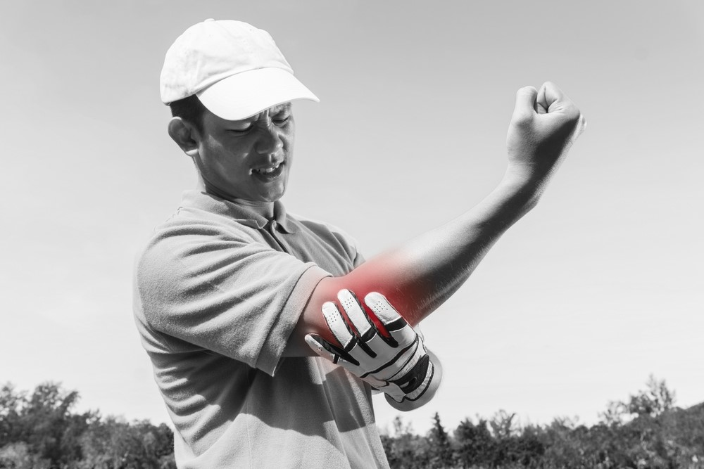 A golfer holding his arm with golfer's elbow