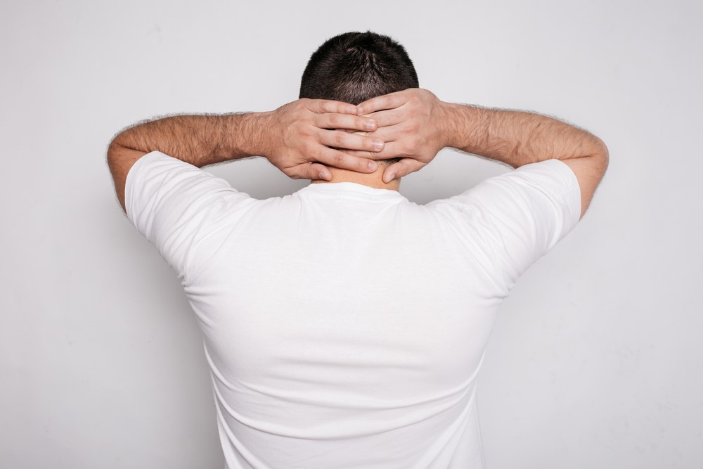 A man with occipital neuralgia holding his head