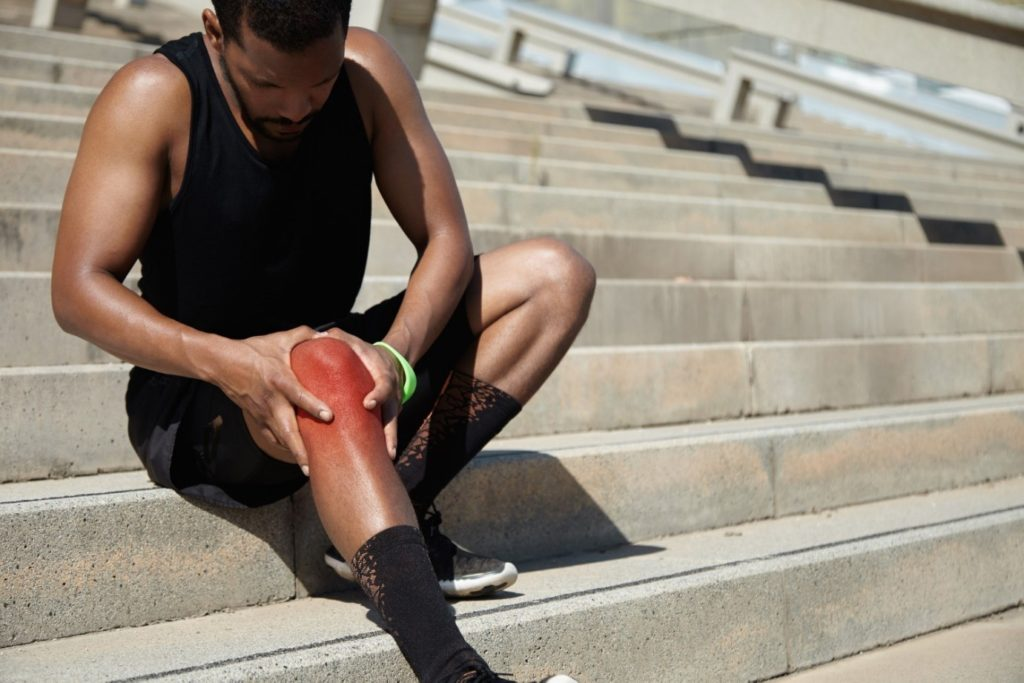 A man with patellar tenidinitis holding his knee