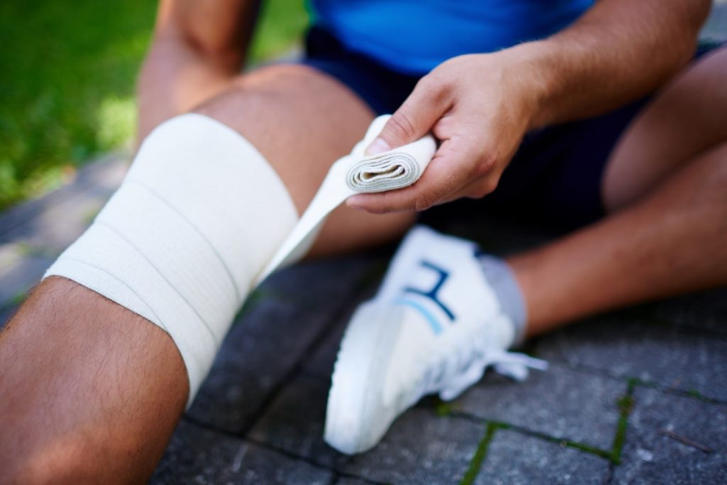 A man with patella tendonitis putting a knee support on