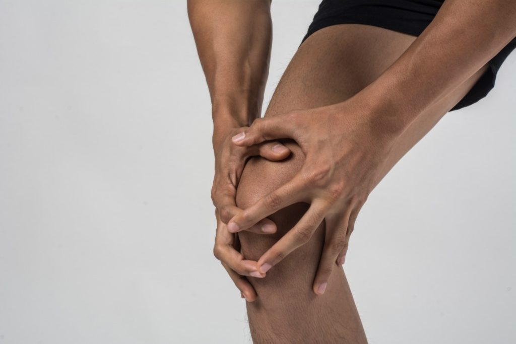 A man with hypermobility holding his knee